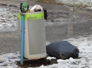 Überquellender Mülleimer mit Rattenköderbox